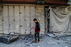 March 26, 2019 - Gaza, Palestine, 26th March 2019. Palestinians assess the damage at the site of the Multazim insurance company building, which was destroyed by Israeli bombardments on the east of Gaza City on 25th March. Israeli warplanes carried out dozens of airstrikes across the southern, central, and northern Gaza Strip after a Gaza rocket struck an Israeli house north of Tel Aviv, in central Israel, injuring seven Israelis. Israeli warplanes targeted Hamas sites, as well as dozens of residential and commercial buildings, and according to the Palestinian Ministry of Health in Gaza, seven Palestinians suffered various injuries due to the airstrikes (Credit Image: © Ahmad Hasaballah/IMAGESLIVE via ZUMA Wire)