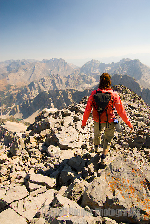 A young woman hikes near the summit of Borah Peak (12,662ft-highest point in Idaho) in the Lost River Range, Idaho.