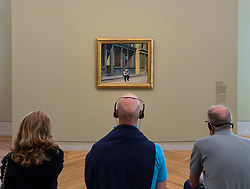 Visitors looking at painting Sunday by Edward Hopper at exhibition of American art , From Hopper to Rothko at the Barberini Museum in Potsdam , Germany . Editorial Use Only