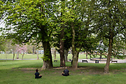 People out meditating and applying social distancing in Canon Hill Park as Coronavirus is felt on a local level on 12th April 2020 in Birmingham, England, United Kingdom. People here, in what is normally an incredibly busy urban park are mainly abiding the stay at home message, and those out exercising are doing so with care. Coronavirus or Covid-19 is a new respiratory illness that has not previously been seen in humans. While much or Europe has been placed into lockdown, the UK government has announced more stringent rules as part of their long term strategy, and in particular social distancing.