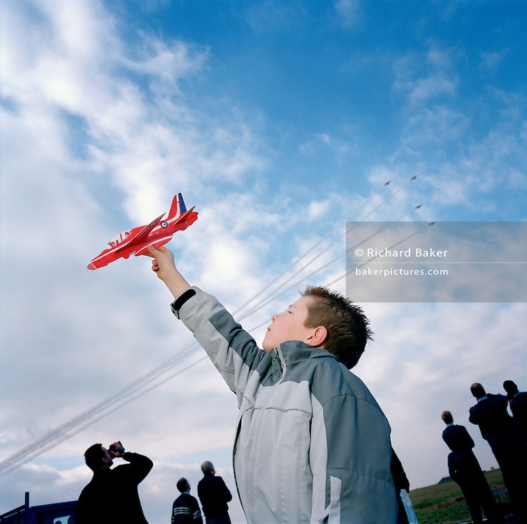 A 7 year-old boy has been lucky enough to spend a day with the elite 'Red Arrows', Britain's prestigious Royal Air Force aerobatic team. As just four members of the team of nine red jet aircraft fly past in formation, Mitchell stretches out his arm, holding a plastic toy Hawk aircraft up to the blue sky and light cloud with his back to the practice show, part of the team's winter training schedule. The Red Arrows' main purpose is Press and PR and corporate guest visitors are a weekly item in the team's diary during the winter training period - a 5-month schedule of up to six flights a day. Companies who help the RAF, the Red Arrows or local charities are privileged to be invited behind-the-scenes at the squadron's home facilities.