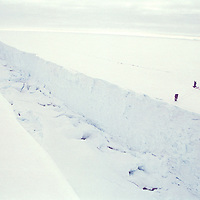 Wide aerial view of two Greenpeace people near canyon sized  crack in the ice, crack runs from bottom right corner to top left corner of frame. Accession #: 2.97.081.001.14