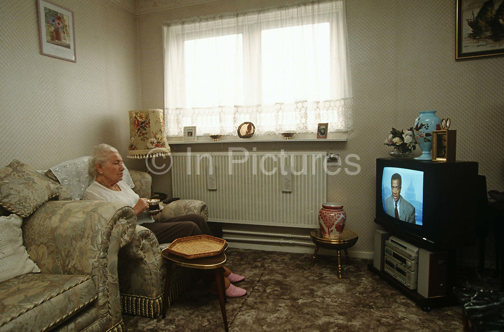 An elderly lady widow resident of a tower block, enjoys the company of TV newsreader in her inner-city home. Watching the television news programme on which a black man of perhaps afro-Caribbean descent is presenting, the lady sits with a cup of tea, wearing pink slippers and surrounded by personal possessions that line the sill of her high-rise window, overlooking the Middlesex Estate in the City of London. She is alone apart from the on-screen presence of the male presenter empty of human contact or friendly neighbours. She lives alone in this inner city flat but she is looking after herself showing brushed hair, a lace top and lipstick. The world outside is a depressingly empty landscape of concrete walkways and garage doors, an inner-city environment devoid of human interaction or friendliness.