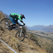 John Stout, UK, in action during the New Zealand South Island Downhill Cup Mountain Bike series held on The Remarkables face with a stunning backdrop of the Wakatipu Basin. 150 riders took part in the two day event. Queenstown, Otago, New Zealand. 9th January 2012. Photo Tim Clayton