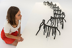 """© Licensed to London News Pictures. 25/06/2018. LONDON, UK. A staff member views an artwork by Rosemarie Castoro.  Preview of """"Lands of Lads, Land of Lashes"""", an exhibition of sculptures and paintings by three female artists of the1960s and 1970s - Rosemarie Castoro, Wanda Czelkowska and Lydia Okumura - specialising in Minimal and Post-Minimal art.  The exhibition, held at Galerie Thaddaeus Ropac in Mayfair, runs 25 June to 11 August 2018.  Photo credit: Stephen Chung/LNP"""