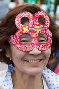 Portrait of a woman wearing paper glasses in the shape of the number 88. One of thousands of people took part in the 88th May Day rally in Central Tokyo to mark International Workers` Day. Tokyo, Japan. Monday, May 1st 2017 The rally started at 9am in Yoyogi Park near Shibuya and the march began at 12:30 despite heavy rain and thunderstorms. The rally called for an end to overwork in Japan along with other labour issues and  protested traditional left wing subjects such as nuclear power and weapons, and Prime Minister Shinzo Abe's plans to reinterpret  Article 9 of the Japanese constitution, thus making the Japanese military Self Defence Force able to fight wars alongside its allies.