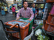 "21 DECEMBER 2015 - BANGKOK, THAILAND:  A man sets up his produce stand in Pak Khlong Talat, also called the Flower Market. The market has been a Bangkok landmark for more than 50 years and is the largest wholesale flower market in Bangkok. A recent renovation resulted in many stalls being closed to make room for chain restaurants to attract tourists. Now Bangkok city officials are threatening to evict sidewalk vendors who line the outside of the market. Evicting the sidewalk vendors is a part of a citywide effort to ""clean up"" Bangkok.      PHOTO BY JACK KURTZ"