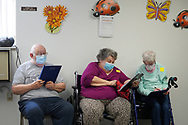 Ken Miller, left, his wife Mary Ellen Miller, and Marion Klein, right, fill out paperwork while they wait to be vaccinated as Lehigh Valley Health Network brought their mobile vaccination clinic to Majestic House on May 6, 2021, which offers low income housing to Seniors 55 years and over, in Tamaqua, Pennsylvania.