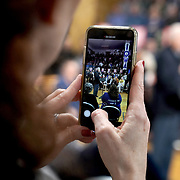 A person takes s photo of Democratic presidential candidate Joe Biden addressing supporters and potential caucus voters during a community event at the Roosevelt Creative Corridor Business Academy in Cedar Rapids, Iowa on Saturday, February 1, 2020.