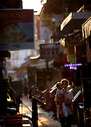 A woman carries a baby through a street cluttered with restaurants in Siem Reap, Cambodia