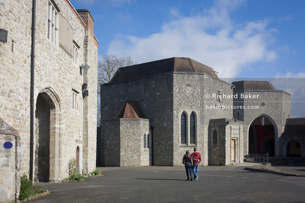 A young couple walk towards the Shrine Altar at Aylesford Priory (Friary) in Kent, England. The structures are not original as the buildings on this Christian ancient site were damaged by King Henry VIII during the dissolution of the monasteries of the 16th century. This structure was repaired after WW2 for the benefit of those pilgrims on retreat at this quiet location in the county of Kent, southern England.