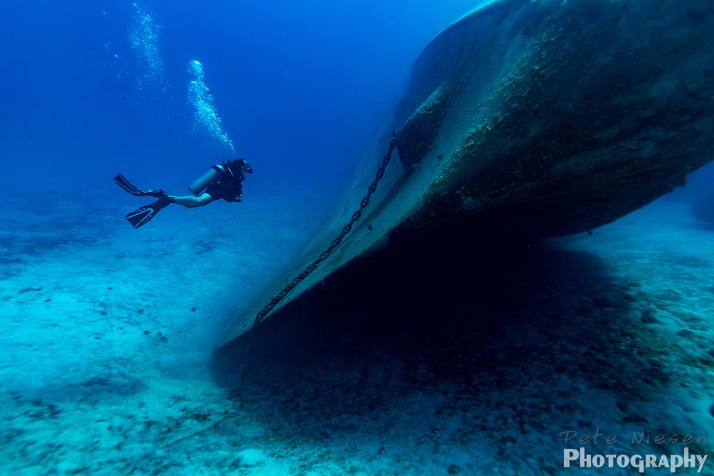 Scuba diver observes the huge hull of sunken shipwreck