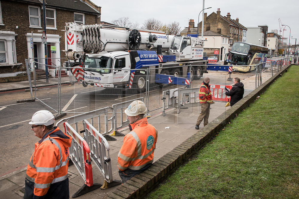 © Licensed to London News Pictures. 27/11/2016. London, UK. Heavy lifting equipment arrives on Lee High Road in Lewisham after a French tourist coach fell into a sinkhole. The road has been closed off and police declared a 'major incident' after the coach with 100 passengers on board fell into a sinkhole caused by a burst water mains, flooding a long stretch of the road including many local businesses. . Photo credit: Rob Pinney/LNP