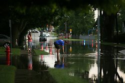 A man tries to unplug a sewer drain on Division Street in Mundelein, Ill. following heavy rains and storms on Wednesday, July 12, 2017. Photo by Stacey Wescot/Chicago Tribune/TNS/ABACAPRESS.COM