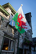 The Welsh Dragon, the national flag of Wales, hangs in evening sunshine outside the the Cross Keys pub, on 12th September 2018, in Dolgellau, Gwynedd, Wales