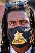 """15 AUGUST 2020 - MINNEAPOLIS, MINNESOTA: A member of MN Freedom Fighters, who provide security at the George Floyd Memorial in Minneapolis. Floyd, an unarmed Black man, was killed by Minneapolis police officers of May 25 in front of Cup Foods, a convenience store at the intersection of 38th and Chicago Ave. His killing sparked a week of violent protests across the country. The intersection where he was killed is still closed and has become an unofficial memorial visited by hundreds of people every day. Saturday, more than 100 people gathered at the memorial to demand the city preserve the memorial. On Saturdays in August, the intersection has a market, with venders selling Afro-centric merchandise. The city of Minneapolis had planned to start reopening the intersection as soon as Monday Aug. 17, but delayed those plans indefinitely on Friday, Aug. 14. City residents have created a """"George Floyd Zone"""" at the intersection. They're demanding the recall of Hennepin County Attorney Mike Freeman, requiring Minneapolis police officers have their own private liability insurance, and the allocation of funds for businesses and residents in the community. The city is considering officially renaming Chicago Ave. between 37th and 39th """"George Floyd Jr. Place.""""     PHOTO BY JACK KURTZ"""