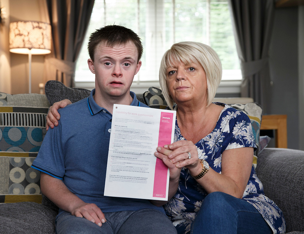 Stuart Chester and mum Deborah McKenzie at home in Springboig ,Glasgow. Severely disabled Stuart McKenzie, 25, who cannot talk, write or read has been sent a 20-page capability for work questionnaire. He is looked after by his mum Deborah 24/7 and there is no way he can work. He has Downs Syndrome, epilepsy and autism.  Picture Robert Perry for 28th Aug 2015<br /> <br /> Must credit photo to Robert Perry<br /> FEE PAYABLE FOR REPRO USE<br /> FEE PAYABLE FOR ALL INTERNET USE<br /> www.robertperry.co.uk<br /> NB -This image is not to be distributed without the prior consent of the copyright holder.<br /> in using this image you agree to abide by terms and conditions as stated in this caption.<br /> All monies payable to Robert Perry<br /> <br /> (PLEASE DO NOT REMOVE THIS CAPTION)<br /> This image is intended for Editorial use (e.g. news). Any commercial or promotional use requires additional clearance. <br /> Copyright 2014 All rights protected.<br /> first use only<br /> contact details<br /> Robert Perry     <br /> 07702 631 477<br /> robertperryphotos@gmail.com<br /> no internet usage without prior consent.         <br /> Robert Perry reserves the right to pursue unauthorised use of this image . If you violate my intellectual property you may be liable for  damages, loss of income, and profits you derive from the use of this image.