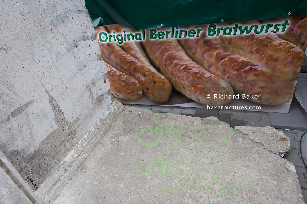 """A poster for original Berliner Bratwurst sausage next to a section of the Berlin wall near the former Checkpoint Charlie, the former border between Communist East and West Berlin during the Cold War. The Berlin Wall was a barrier constructed by the German Democratic Republic (GDR, East Germany) starting on 13 August 1961, that completely cut off (by land) West Berlin from surrounding East Germany and from East Berlin. The Eastern Bloc claimed that the wall was erected to protect its population from fascist elements conspiring to prevent the """"will of the people"""" in building a socialist state in East Germany. In practice, the Wall served to prevent the massive emigration and defection that marked Germany and the communist Eastern Bloc during the post-World War II period."""