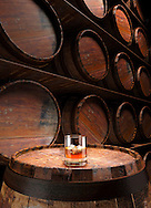 Rye Whisky In Glass On Barrel In front Of Wall Of Barrels