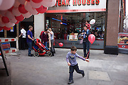 A young boy runs with a red balloon as his family and friends continue their day trip to London.