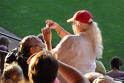 Fan shooting a photo in the bleachers. Furthur Band at McCoy Stadium, Pawtucket RI on 5 July 2012