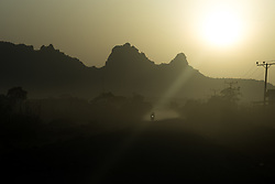 27 January 2019, Bale Zone, Oromia, Ethiopia: A motorbike rides the road from Ginnir to Micha in the Bale Zone of Ethiopia, as the sun rises over the Hussein Bule mountains, named after an old warrior and freedom fighter who was known to use the mountains as a hiding place.