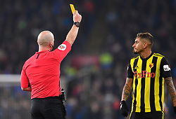 Referee Roger East (left) shows a yellow card to Watford's Roberto Pereyra during the Premier League match at the Cardiff City Stadium.