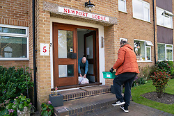 Tony Rosa delivers food packages from Enfield Council to Peter Hetherington in Enfield, north London.