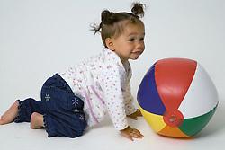 Baby crawling towards beach ball on the floor,