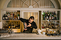 GARDONE RIVIERA, ITALY - 20 APRIL 2018: Rama Redzepi, Bar Manager of the Grand Hotel Fasano, prepares a Cover Club cocktail (gin, lemon, sugar and rasberry) at La Terrazza (the terrace) of the hotel  in Gardone Riviera, Italy, on April 20th 2018.<br /> <br /> Lake Garda is the largest lake in Italy. It is a popular holiday location located in northern Italy, about halfway between Brescia and Verona, and between Venice and Milan on the edge of the Dolomites. The lake and its shoreline are divided between the provinces of Verona (to the south-east), Brescia (south-west), and Trentino (north).