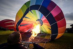 A balloon pilot checks his burner and inflates the balloon in preparation for flight from Clifton Downs, Bristol, as balloonists gather to mark less than a week to go until the start of the Bristol International Balloon Fiesta.
