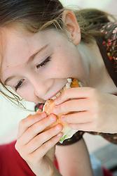 Young girl tucking into a hamburger,