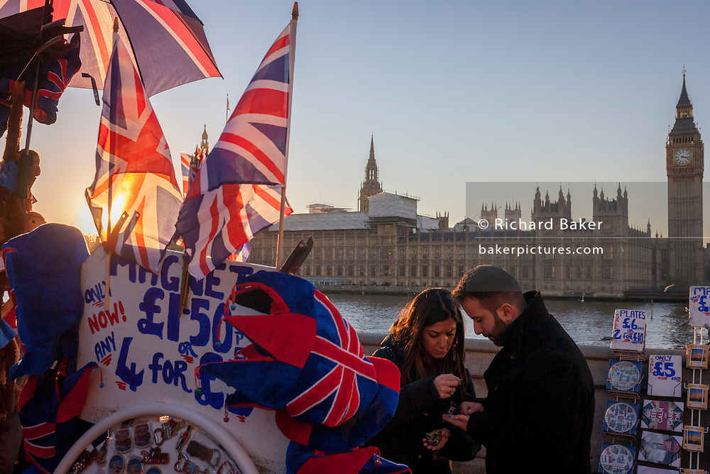 Tourists find the right coins by British union jack flags, Big Ben and the Houses of Parliament in the distance, on 29th November 2016, in London, England.