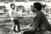 Atlanta police officer Freddie Baker talks with a child who was wandering unattended at Atlanta's east Lake Meadows public housing neighborhood during the period of tthe Atlanta Child Murders.