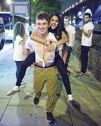 """© Licensed to London News Pictures . 22/10/2012 . Manchester , UK . A male student gives a female student a piggy back through the crowd . Students attend a Carnage UK pub crawl at bars in Manchester 's Deansgate Locks with a fancy dress theme of """" Pimps and Hoes """" . The event has been criticised for encouraging binge drinking , sexism and anti-social behaviour . Photo credit : Joel Goodman/LNP"""
