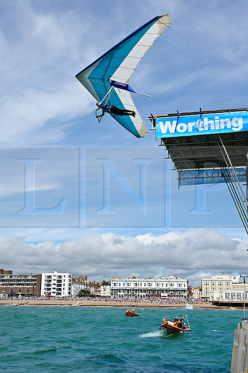 © Licensed to London News Pictures. 13/08/2011. Worthing, UK. A flyer jumps from Worthing pier, 35ft above the water aiming to fly over 100M and win the £10,000 price for the longest flight over 100M. This first flight measured 61M. Flying was cancelled due to high winds. Sundays (14th) event will also include fun flyers raising money for charity.  Photo credit : Julie Edwards/LNP