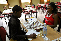 Phiona Mutesi, left, a 14-year-old chess prodigy, plays chess in Kampala, Uganda, Dec. 11, 2010. Mutesi lives in the slums of Uganda and is just now learning to read. But her instincts have made her a player to watch in international chess. Mutesi, a naturally talented chess player is coached by Robert Katende of Sports Outreach Ministry. The chess club meets at the Agape Church inside Katwe, the largest slum in Kampala.