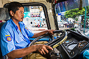 19 JUNE 2013 - YANGON, MYANMAR: A Yangon bus driver navigates city traffic. Yangon buses are generally overcrowded and in poor repair but as the economy improves newer, but still used, Japanese and Korean buses are being imported. Hundreds of bus routes criss-cross Yangon, providing the cheapest way of getting around the city. Most fares are less than the equivalent of .20¢ US.   PHOTO BY JACK KURTZ