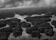 Lac de retenue du barrage de Petit-Saut, Guyane, 2015.<br /> <br /> Survol du lac de retenue du barrage de Petit-Saut.<br /> <br /> Pour répondre à la forte augmentation des besoins énergétiques de la Guyane au début des années 1980, le barrage de Petit-Saut est construit sur le fleuve Sinnamary et mis en service en 1994. Sa retenue d'eau s'étend sur 310 km². Compte tenu de la taille de la forêt à inonder, il n'a pas été procédé à la déforestation du site. Vingt ans après son ouverture le spectacle est apocalyptique. Très controversé pour les impacts qu'il engendre (émissions de gaz à effet de serre, disparition de la biodiversité forestière, perturbation du cycle du mercure et du milieu aquatique, peu de création d'emplois), sa production en énergie électrique ne suffit déjà plus à l'accroissement de la population et de ses besoins.<br /> <br /> Une route a été construite pendant le chantier du site pour permettre aux camions d'arriver jusqu'au site. Elle relie RN1 au barrage et en constitue la seule voie d'accès. Rétrocédé à l'État par EDF, qui en était originellement propriétaire, cet axe de 27 km tracé dans la forêt n'est que très peu entretenu. En 2001, le préfet de l'époque ferme l'accès de cette piste forestière aux particuliers. Aujourd'hui encore, seules les personnes habilitées peuvent l'emprunter. Dans la pratique, en dehors de l'hélicoptère, la route reste l'unique moyen de se rendre à Saint-Élie, en naviguant sur le lac.
