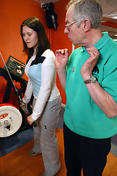 Instructor showing young woman how to use weights at an inclusive fitness gym,