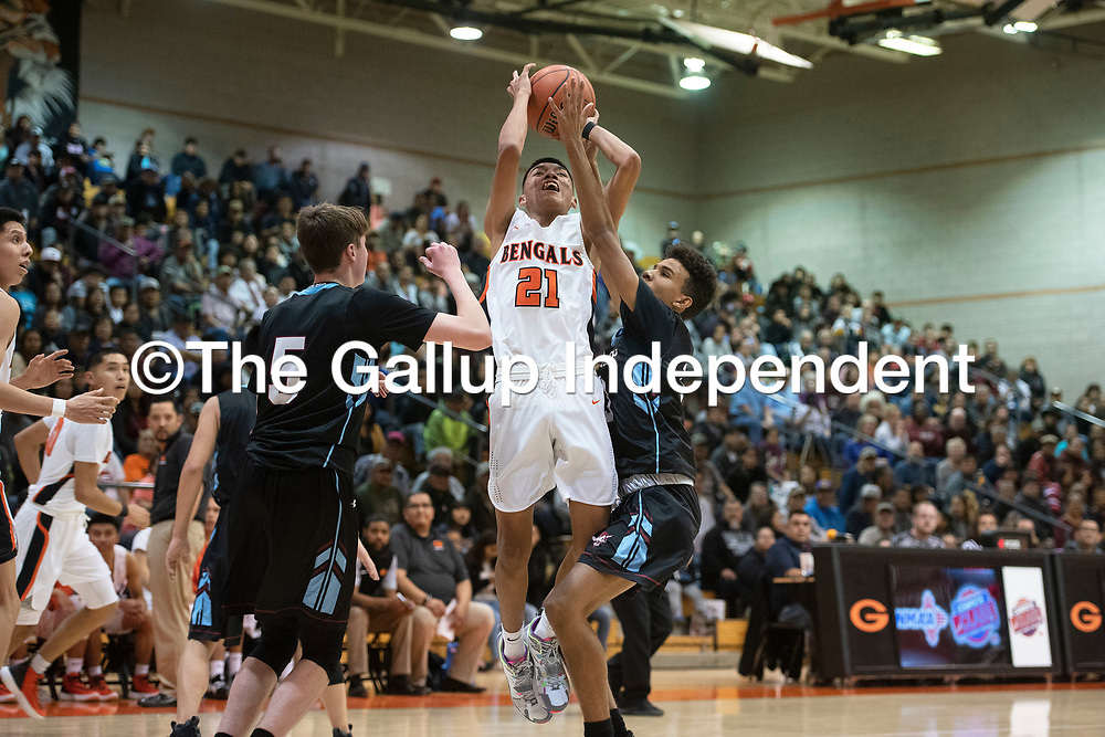 Gallup's Jeffery Yazzie (21) takes a jump shot against  Sandia Prep Friday night at the Gallup Invitational boys basketball tournament at Gallup High School. Gallup beat Sandia Prep 61-60.