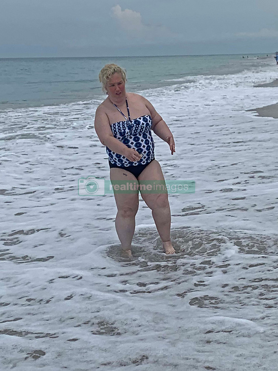 """EXCLUSIVE: Mama June jogs on a beach in a swimsuit as she ramps up her weight loss campaign. The reality star, 40, is determined to lose 45lbs and has been doing yoga sessions and long walks to try and meet her weight goal. The mother-of-four was pictured at Jensen Beach, Florida where she showed off her new keep fit plan. A friend, who revealed June has lost 20lbs so far, said: """"June has really been focusing on her fitness to try and shed some of the pounds she put on. She's been doing a lot of yoga and jogging in the mornings on the beach. """"She has been training everyday with her close friend artist Adam Barta."""" June once weighed 460lbs but lost a staggering 300lbs after an intense exercise regime coupled with gastric and plastic surgery. Since tipping the scales at 160lbs she has now put on some extra weight and is bidding to lose an extra 45lbs. 02 Jun 2020 Pictured: Mama June jogs on a beach in a swimsuit as she ramps up her weight loss campaign. Photo credit: MEGA TheMegaAgency.com +1 888 505 6342"""