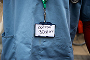 Hackney London February 10th 2016. Second one day strike by junior doctors  protesting against proposed changes to their contract including payment for working on Saturdays. Picket at Hackney Town Hall . A Junior doctor has a sign, in place of his name tag, saying 'doctor 30% off' refencing the drop in salary doctors expect under the new contract.