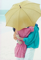 Kissing couple hidden under an umbrella