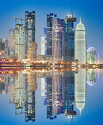 Night view of skyline along waterfront of Corniche towards modern office towers in Doha Qatar