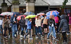 © Licensed to London News Pictures. 26/07/2019. London, UK. Members of the public brave wet and grey conditions at Buckingham Palace in Westminster, central London as the capital is deluged with rain, following a week that saw the UK experience record temperatures for July. Photo credit: Ben Cawthra/LNP