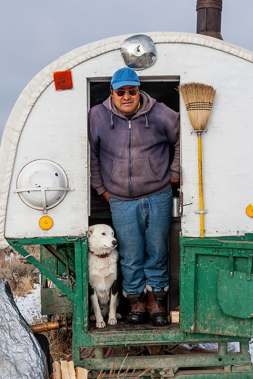 Lucas a sheepherder with his dog in Sheepwagon in the Sawtooth Valley in Central Idaho. Licensing and Open Edition Prints.
