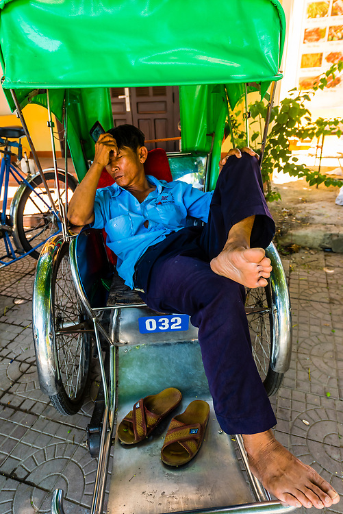 A cyclo driver taking a nap. A cyclo (in Vietnamese xich lo, is a three wheeled bicycle taxi), Old Town, Hoi An, Vietnam.