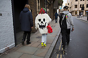 Woman wearing a fur coat with an evil face on it. London, UK.