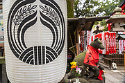 A traditional paper lantern and statue of Inari Kitsune or fox goddess, at the Toyokawa Inari Betsuin temple in Asakusa, Tokyo, Japan. The Buddhist temple is part of the Soto Zen sect and enshrines the deity Toyokawa Dakinishinten but also known for the thousands of fox statues.